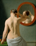 Naked woman doing her hair before a mirror